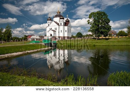 White Beautiful Orthodox Church In Front Of The Lake On A Sunny Summer Day