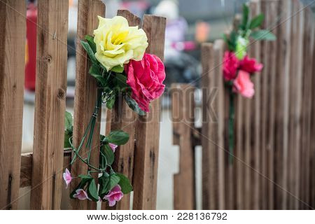 Artificial Bouquet Of Flowers On A Wooden Fence