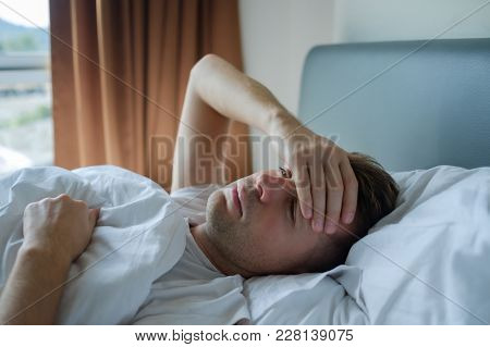 Caucasian Man Lying In Bed At Home Suffering From Headache Or Hangover. Concept Of Problem With Heal
