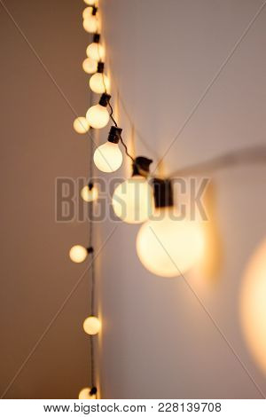Garland With Lamps On A White Wall In The Apartment