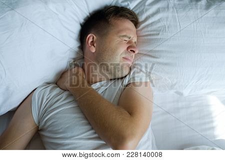 Caucasian Young Man Having Terrible Pain In Neck In Bed In The Morning. Concept Pf Health Problems W