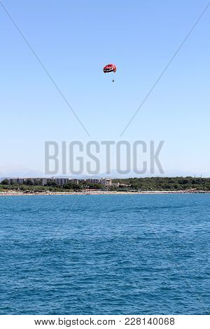 People Fly By Parachute In The Blue Sky Over The Sea In Clear Weather, A Holiday At Sea, Parachute F