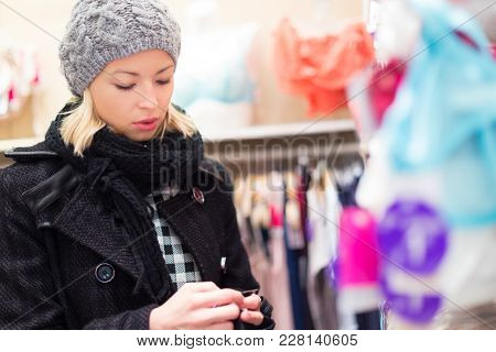 Woman Shopping Lingerie . Shopper Looking And Choosing Clothing Indoors In Store. Beautiful Blonde C