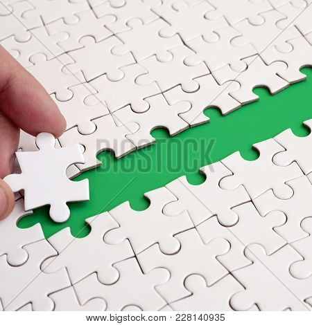 The Human Hand Paves The Way To The Surface Of The Jigsaw Puzzle, Forming A Green Space. The Concept