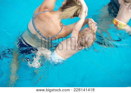 Happy Little Sports Man Has Swimming Lesson With Mother - Active Baby Swim With Fun In Woman Hands I