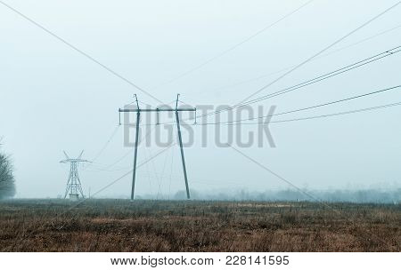 High Voltage Lines And Power Pylons In In The Countryside In The Early Spring On The Outskirts.