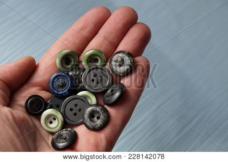 A Bunch Of Old Colored Buttons On An Open Palm Above The Table