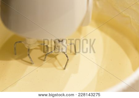 A Kitchen Mixer With Yellow Egg Yolks Mixed With Sugar In A Modern Kitchen. Shot At An Angle With Th