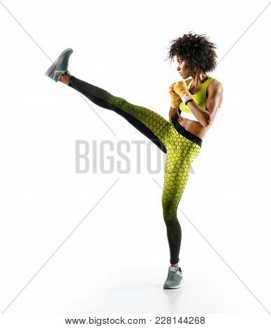 Girl Practicing Tae-bo Exercises, Kicking Forward With Legs. Photo Of Sporty African Girl On White B