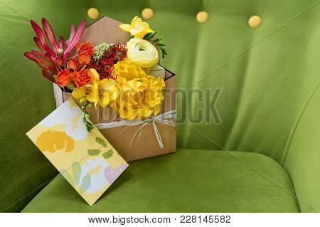 Giftbox With Flowers And Greeting Card. Colorful Spring Bouquet In Wooden Box On Green Soft Armchair