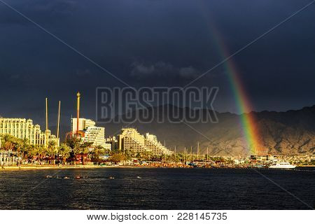 Rainbow And Dark Rain Clouds Over Lightened Beach And Hotels In Eilat, Israel. Aqaba Gulf In Red Sea