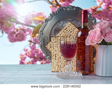 Passover Holiday Celebration Concept With Wine, Matzo, Flowers And Seder Plate Over Spring Backgroun