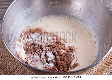 Preparing A Dough/batter For Crepes Or Pancakes With Wheat Flour And Cocoa In Bowl, Milk, Eggs
