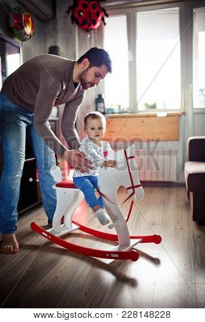 The Young Father Is Playing With His Little Daughter In The Room. Happy Family Concept. Vertical