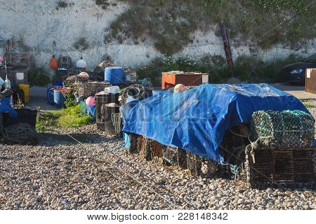 Fishing Gear And Crab Traps Are Stacked On The Beach. Beer. Devon. Uk