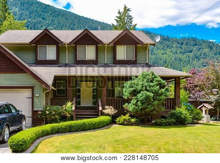 Big Family House With Hedge And  Draw-well Decorating The Front Yard On Mounting And Blue Sky Backgr