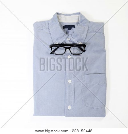 Glasses Lie On The Blue Neatly Folded Men Shirt With A Long Sleeve Instead Of A Bow Tie