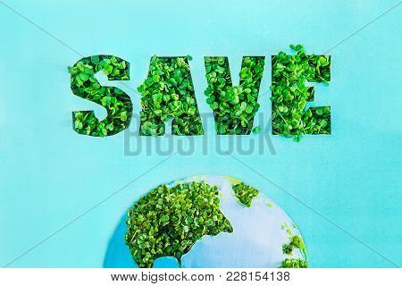 Creative Concept With Outline Lettering Save In Green Fresh Grass Sprouts And Part Of Planet Model O