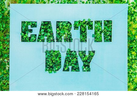 Creative Concept With Blue Turquoise Paper Blank With Outline Lettering Earth Day In Green Fresh Gra