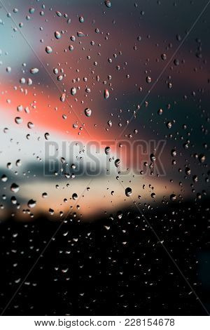 Raindrops On Window In Front Of Beautiful Colored Out Of Focus Sky