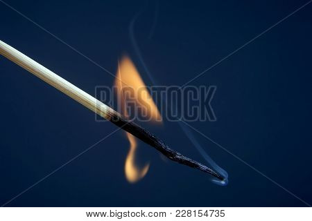 The Burning Match On A Dark Background