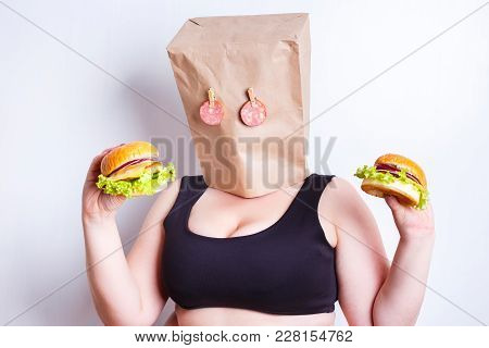 Obese Fat  Woman With A Paper Bag On Her Head Like A Mask With Eyes Made Of Salami As A Symbol Of Fo