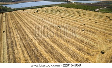 Aerial Flight View Of A Cube Baler Tractor Discharges A Fresh Wheat Bale During Harvesting.agricultu
