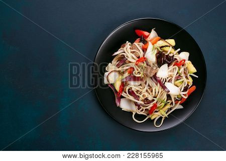 Udon Wok Noodles With Pork And Peppers, Served On Black Plate, Flat Lay With Copy Space. Japanese Cu