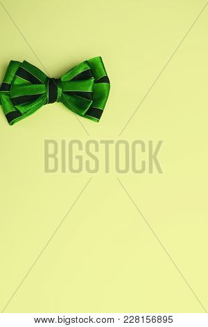 Green Bow Tie With Black Stripes On Bright Yellow Background. Template For Greeting Card With Copy S