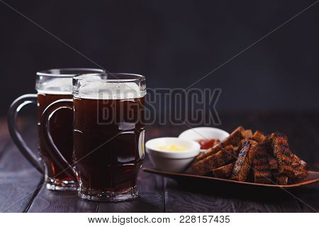 Two Mugs Of Stout And Crunchy Rye Toasts, Served With Tomato And Cheese Sauces, Close Up. Oktoberfes