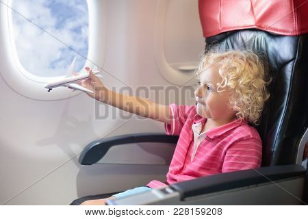 Child Flying In Airplane. Flight With Kids.