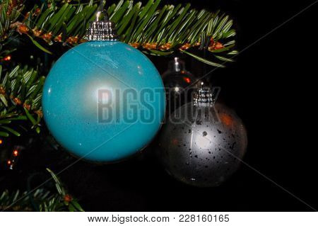 Blue And Silver Baubles Hanging On Christmas Tree Branch