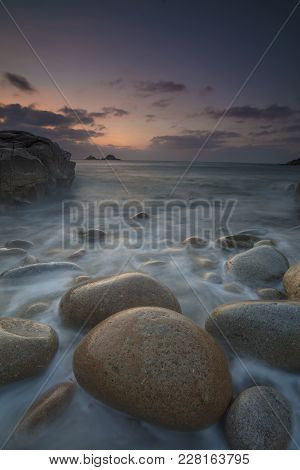 Boulders on Porth Nanven beach looking towards the Brisons at sunset Cot Valley near St Just Cornwall poster