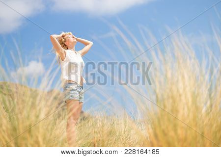 Relaxed Woman, Arms Rised, Enjoying Sun, Freedom And Life An A Beautiful Beach. Young Lady Feeling F
