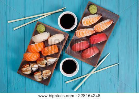 Delicious Set Of Nigiri Sushi Served With Traditional Soy Sauce And Chopsticks, Flat Lay On Blue Pla