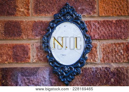Number One Plate On Brick Wall, English Village, Number One.