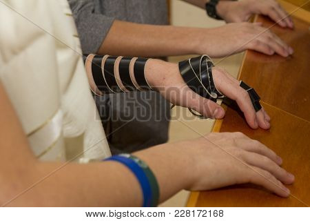 A Young Man Using A Jewish Tefillin On His Arm And Wearing Prayer Shawl For Praying