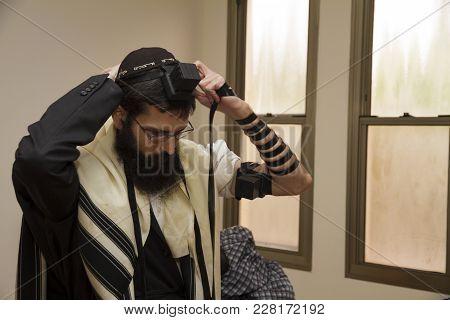 Tel Aviv, Israel - 19 January, 2018: An Adult Jewish Orthodox Man Putting A Jewish Tefillin On His H