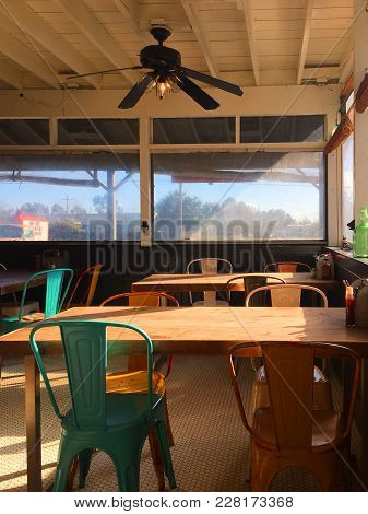 Sunlit Light-filled Rustic American Cafe Restaurant Dining Room Interior With Big Picturesque Window