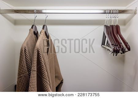 Clothes Hangers And Brown Shower Gown In Clothes Chest, Close Up Of Clothes Hanger And Bathrobe In W