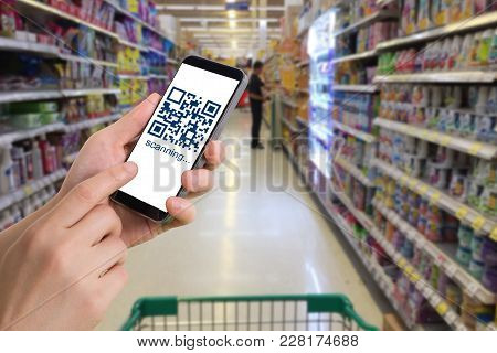 Human Hand Hold And Touch Smart Phone, Tablet, Cellphone With Qr Code Number On Products Shelf Store