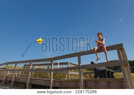 Boy On The Beach With A Kite. Child Launches A Kite On The Seashore. Copy Space For Your Text
