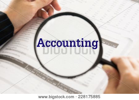 Accounting Concept. Accountant Or Auditor Using Magnifier Checking Annual Financial Statement Of Com
