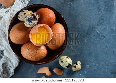 Header With Raw Brown Hen And Quail Eggs, Whole And Broken, On A Wooden Dish. Concrete Background Wi