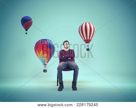 Young Man Looking At Color Hot Air Balloons. The Concept Of Creative Mind.