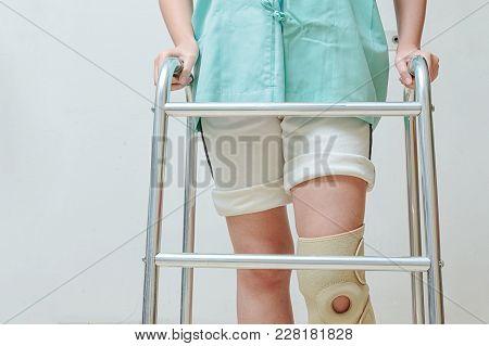 Woman In Knee Support Walking On Walker
