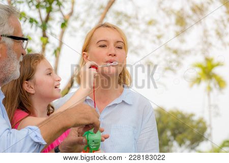 Happy Family Picnic. Grandmother And Grandfather Blow Soap Bubbles Along With Grandchildren On Summe