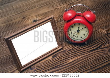 Photo Frame With Copy Space And Retro Style Red Alarm Clock On Wooden Table Background.