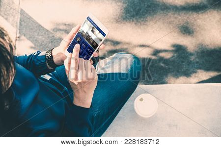Woman Sitting And Use Smart Home Control App On Mobile Phone And Drink Take Away Coffee Outside Hous