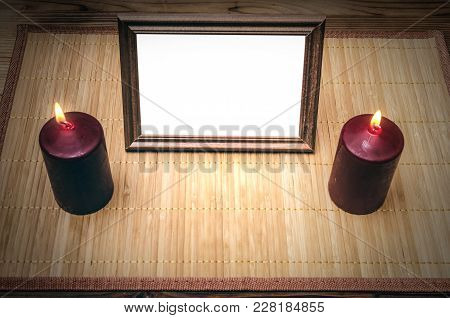Empty Blank Photo Frame Between Two Burning Candles On Bith Side On Wooden Table Background.